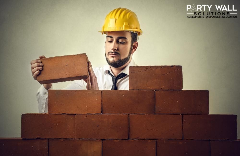 What qualifications does a party wall surveyor require?